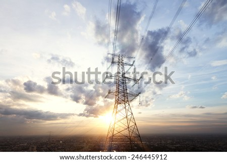 high voltage pylon in field with skyline - stock photo