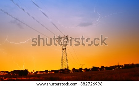 high voltage pylon with lightning in the sky in the night - stock photo