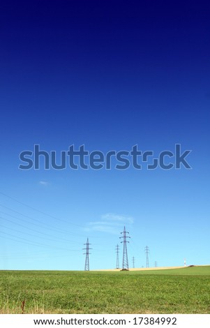 High voltage pylons at spring/summer countryside and blue sky