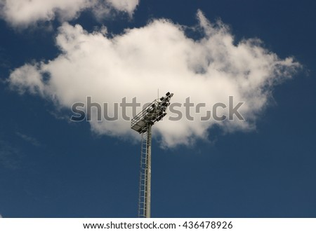 High voltage spotlight pole for sport stadium by cloud and blue sky background