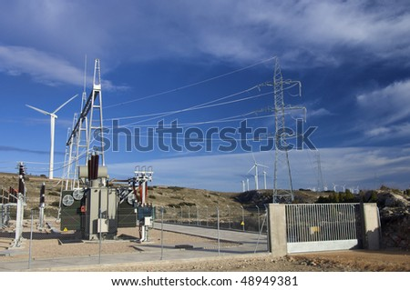 high-voltage substation and windmill with blue sky in Spain - stock photo