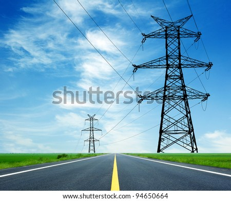 High-voltage tower across the highway - stock photo