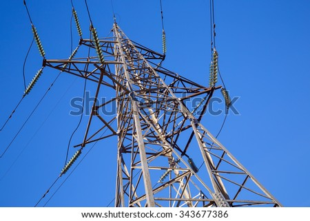 High voltage tower against the blue sky. Electricity transmission pylon