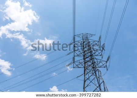 High voltage tower and electrical lines with blue sky background.
