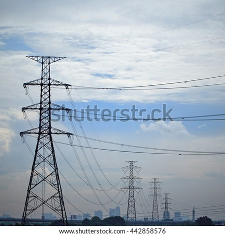 high voltage tower and electricity pylon through town silhouette against blue sky and clouds in background
