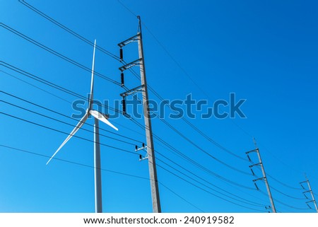 High-voltage tower and wind turbine machine with blue sky background. - stock photo