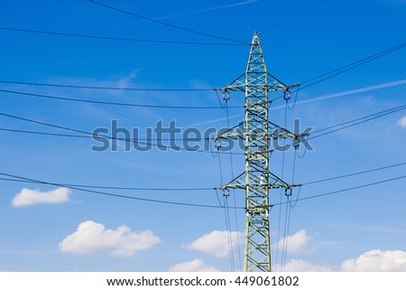 High voltage tower (electricity post) against blue sky with white clouds - stock photo