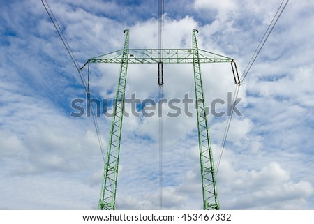 High voltage tower (electricity post) against blue sky with white clouds. - stock photo