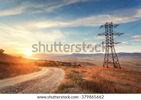 High voltage tower in mountains on the background of colorful sky at sunset.  Electricity pylon system. Summer evening. Industrial landscape  - stock photo