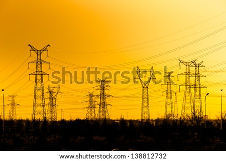 High voltage towers aganist the sunset background. - stock photo