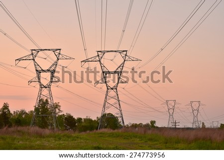 High voltage towers and power lines at twilight - stock photo