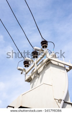 High-voltage transformer close up on blue sky background - stock photo