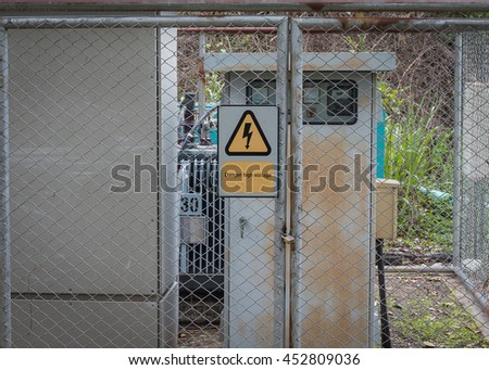 High voltage transformer substation with Danger High Voltage sign. - stock photo