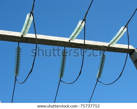 High voltage transmission power line and glass isolators over blue sky background - stock photo