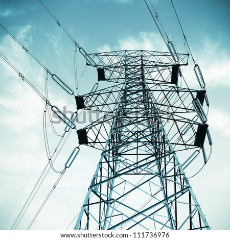 high voltage transmission pylon on blue sky background - stock photo