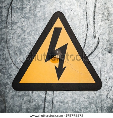High voltage triangle sign mounted on gray metal wall - stock photo