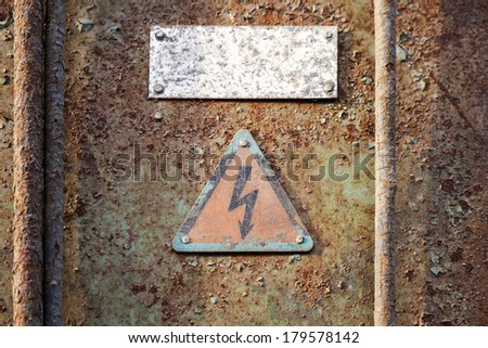 High voltage triangle sign mounted on grunge metal wall - stock photo