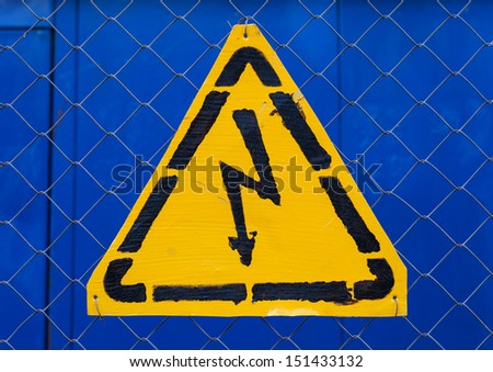 High voltage yellow sign mounted on blue metal rabitz grid - stock photo
