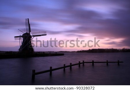 High water levels and a storm on the horizon at a Dutch windmill. - stock photo