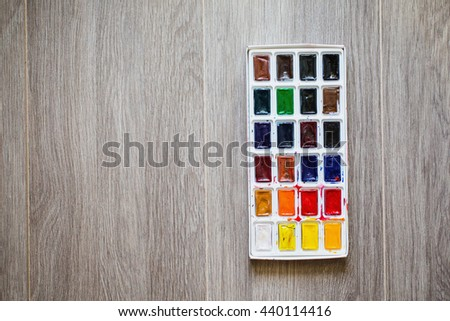 High water watercolor paints on wooden background. Tools for drawing artists. Palette of twenty-four colors. Used paint. A set of warm and cool colors. Vintage texture. Tool to perform drawing work - stock photo