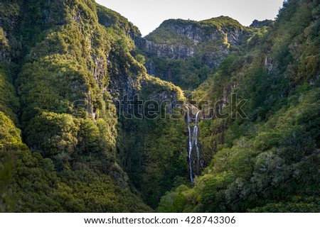 High waterfall in the mountains with evening sun beams on the rocks. The final destination of popular hiking route called levada 25 fountains. Rabacal, Madeira island, Portugal.