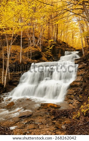 high waterfall in the natural park in autumn - stock photo