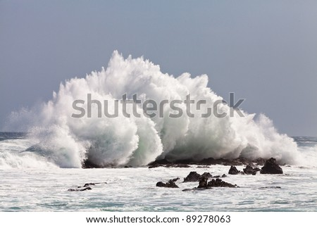 High wave breaking on the rocks of the coastline - stock photo
