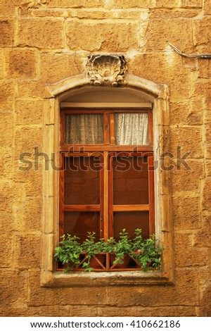 High window with flowers on the windowsill in the city of Valletta - the capital city of Malta.  - stock photo
