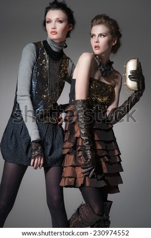 high Young fashion two girl wearing elegant black clothes on gray background  - stock photo