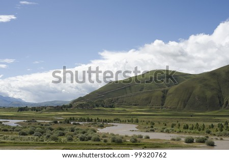 highland lake under the blue sky and white clouds. - stock photo