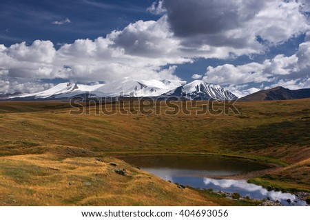 Highland little round lake on the background of high snow mountains under the blue sky and white clouds, Plateau Ukok, Altai mountains, Siberia, Russia