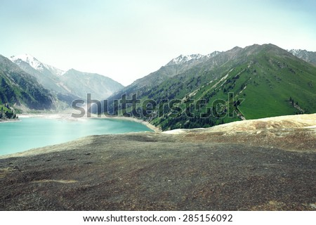 Highland mountain lake view with empty rock in foreground - stock photo