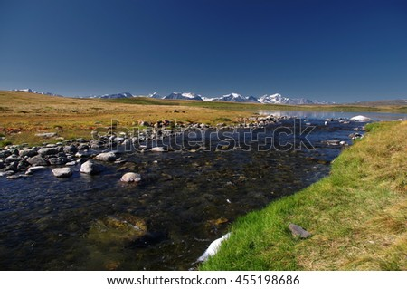Highland river stream flowing from lake on a plateau on the background of mountains with snow and glaciers under clear blue sky Ukok, Altai Siberia, Russia - stock photo