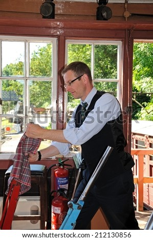 Highley, UK - July 10, 2014 - Signalman operating the Main Line lever on the mechanical lever frame inside the signal box at the railway station, Highley, Worcestershire, England, UK, July 10, 2014.