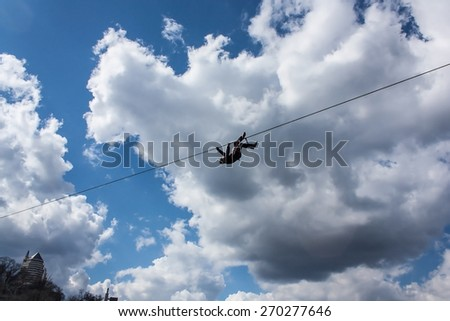 Highliner hanging on tight rope after fall on vibrant blue sky background - stock photo
