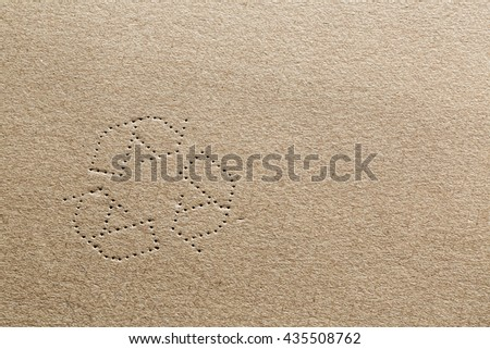 Highly detailed photograph of cardboard surface with the shape of the recycling symbol punched into the carton material.