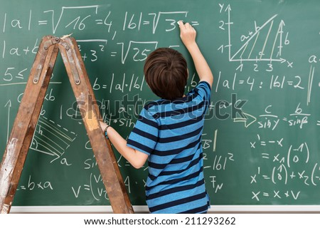 Highly intelligent little boy in the classroom standing on a stepladder to reach a complex mathematical problem on the blackboard that he is busy solving - stock photo