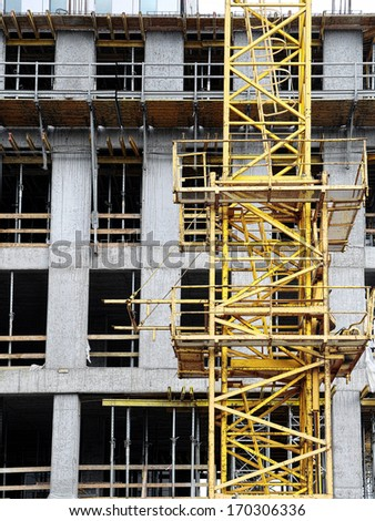 Highrise building under construction with yellow jib crane - stock photo