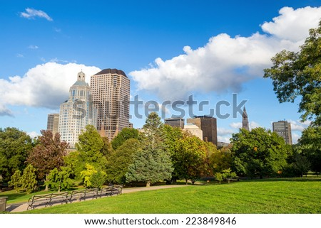 Highrise buildings along Bushnell park, downtown Hartford with blue sky - stock photo