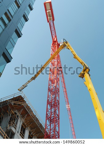 Highrise buildings under construction and two jib cranes over clear blue sky - stock photo