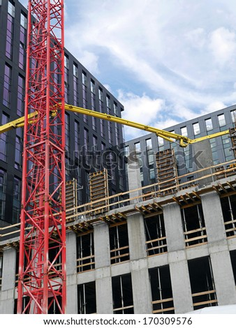 Highrise buildings under construction and yellow ready mix concrete pump to supply concrete mix up above - stock photo
