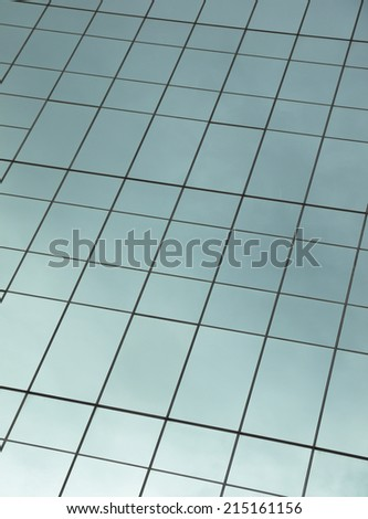 highrise glass building with sky and clouds reflection - stock photo
