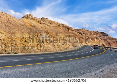 Highway along mountains of Arava desert under beautiful cloudy sky in Israel. - stock photo
