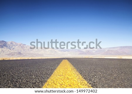 Highway And Mountains At Sunset Highway Toward Death Valley, California, USA - stock photo