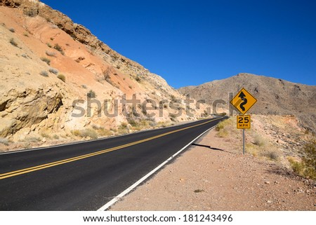 Highway and traffic sign in the yellow desert of Nevada