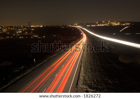 Highway at night between two cities - stock photo