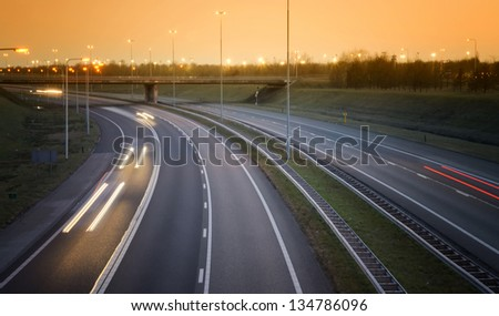 highway at sunset with evening traffic in the Netherlands - stock photo