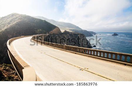 Highway between mountains and pacific ocean. Bixby Bridge at Big Sur