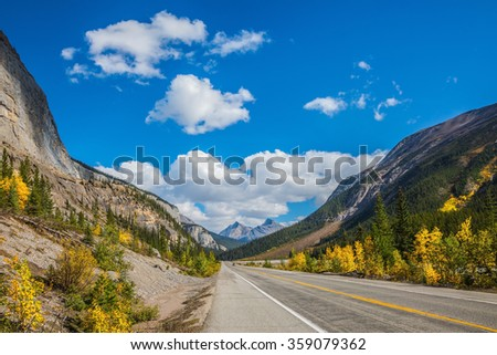 Highway in Banff National Park. Canada, Alberta, Rocky Mountains. Magnificent mountains lit afternoon sun - stock photo