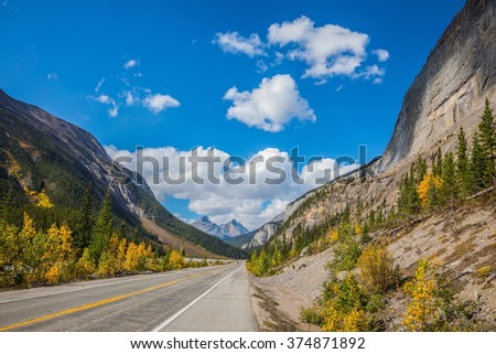 Highway in Banff National Park. Magnificent mountains lit afternoon sun. Canada, Alberta, Rocky Mountains - stock photo